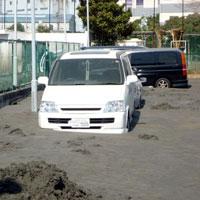 液状化でタイヤが半分埋まった車。新木場地区